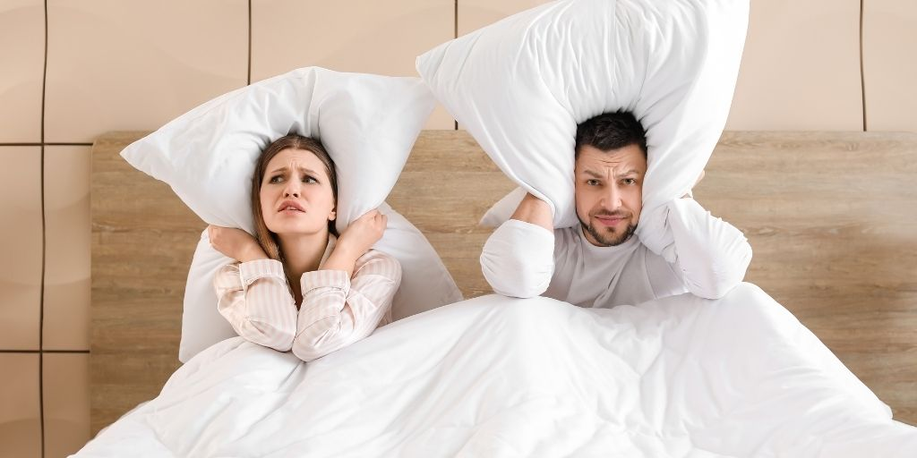 couple with pillow over ears