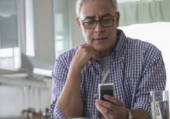 Hispanic man using cell phone in kitchen